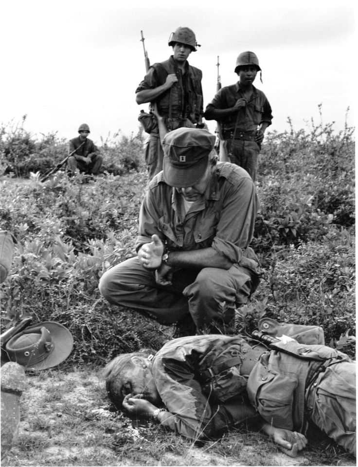 Nov 4, 1965.  Chaplain John McNamara administers the last rites to photographer Dickey Chapelle in South Vietnam.  She became the first female war correspondent to be killed in Vietnam and the first American female reporter to be killed in action.  She was given a full marine burial.  Photo by Henri Huet who was later killed in action in Vietnam.