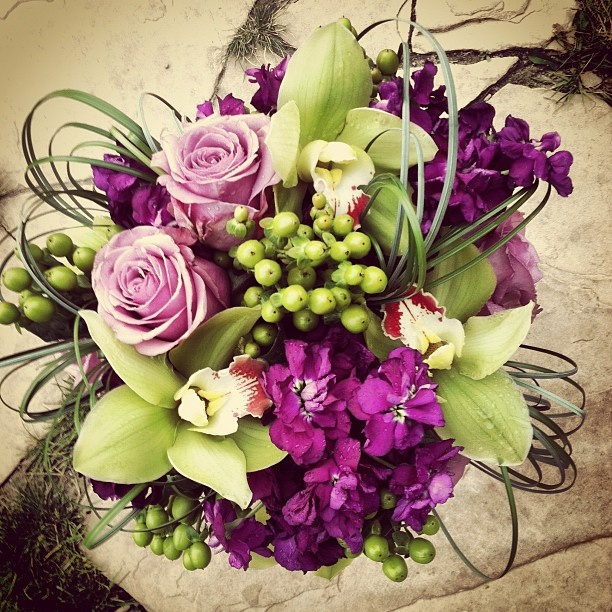 Bride's flower selections included Roses, Orchids, Stock, Hypericum Berry and Bear Grass. Bouquet by http://petalandbean.com