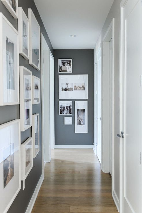 Beautiful hallway boasts dark gray accent walls painted Benjamin Moore Kendall Charcoal studded with photo gallery wall in white gallery frames across from adjacent wall painted light gray.