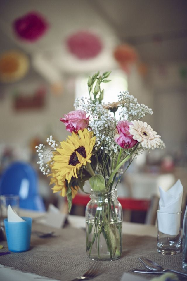 Sunflower Gerbera Rose Flowers Tables Centrepiece Jars Family Friendly DIY Village Hall Wedding http://www.novaweddingphotography.co.uk/