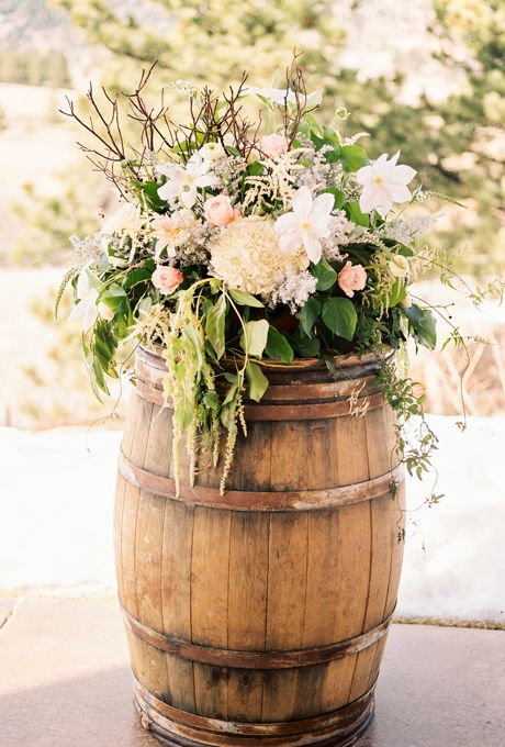 Brides.com: . A wild spray of greens, white hydrangeas, blush roses, and twigs, arranged by Hana Style Designs, balances out the rugged wood of the barrel.