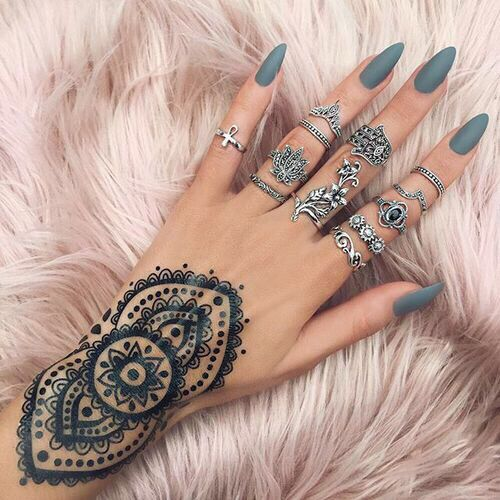 Girl with henna design on her wrist & wearing rings
