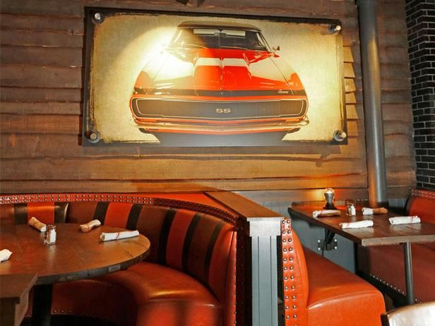Guy Fieri's NYC Restaurant : Three portraits of the red Camaro from Diners, Drive-ins and Dives hang in the bar.