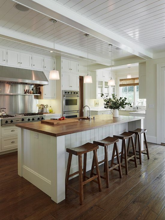 Modern cottage kitchen with glossy white beadboard ceiling and white box beams. White wood paneled center island with butcher block countertop and sawhorse counter stools. Love the chocolate wood floors.