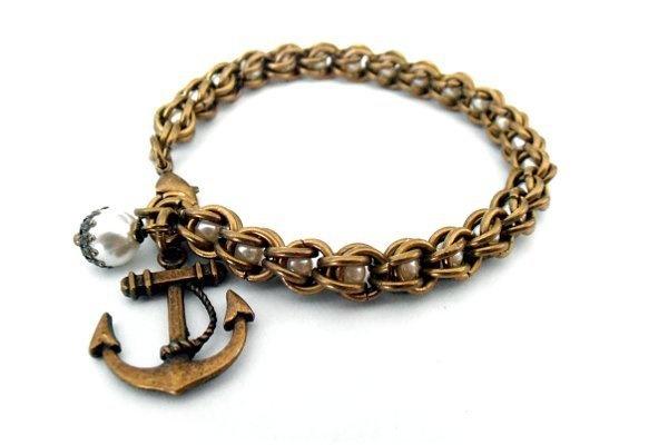 Bronze Armband mit Cremefarbenen Glaswachsperlen und Anker Anhänger. Zwischen den Bronzefarbenen Ringen sind die Perlen eingeschlossen und werden ...