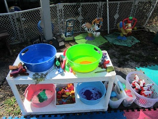 Paint station with circular bins that have paint inside, various brushes, some tree branch pieces for painting with, scrubby brushes for painting with, tempera paint in no spill cups, various foam shapes and  alphabet foam letters, liquid water colors in spray bottles for Free Painting