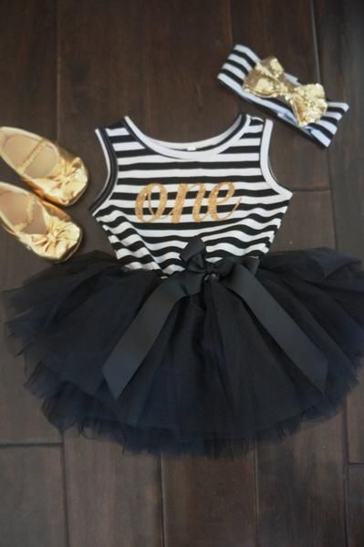 "This gorgeous tutu dress features a gold shimmery ""One"" on black and white stripes. Tutu is black and has an off center black ribbon bow around the waste. This is just for the dress only. Dress is a size 12 months.    We also offer this in a size 12-24 Months with a gold number ""Two""    NUMBER ""ONE"" IS READY TO SHIP Number ""Two"" will take normal shipping time"