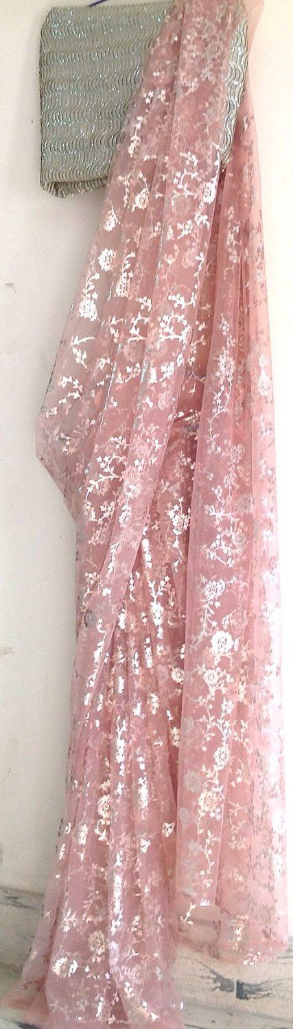 Soft blush pink net saree with all over silver print paired with an embroidered silver sequin blouse. Saree fabric is light soft net in a