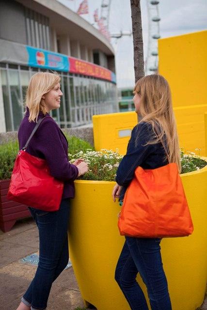 medium red leather handbag on left, large orange leather handbag on right