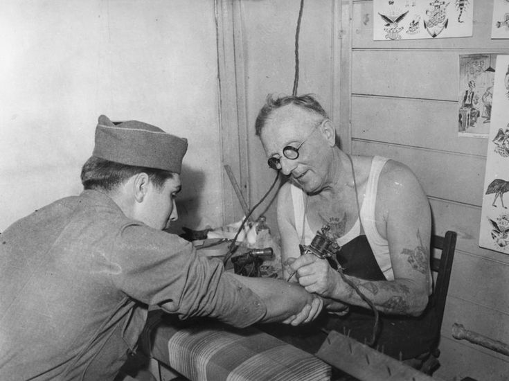 """Young American soldier gets his first tattoo, Brisbane, 1943  It wasn't that local girls... were any more desirable to Americans than the wives or sweethearts back home... """"One Yank who'd hooked up with an Australian girl got a letter from his girlfriend asking what have Australian girls got that American girls haven't got? He wrote back saying, 'Nothing - only they've got it here.'"""" John Oxley Library, State Library of Queensland Neg: 64349"""