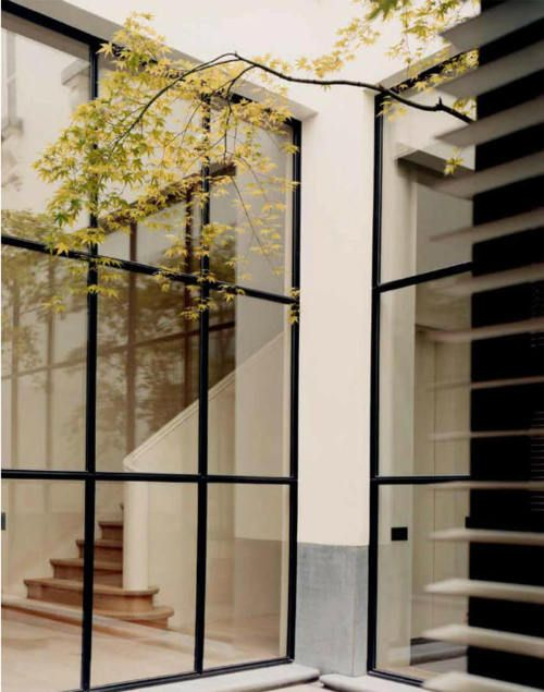 Kombinasi warna: dinding putih, aksen coklat kayu di skirting dan tangga, steel frame hitam. Ciamik.