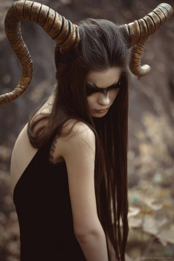 Horned woman. Fabulously-crafted horns. The model's long, straight hair and dark eye makeup paired with it must be quite a sight.