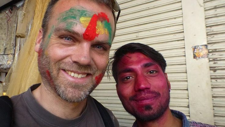 Reporter Jürgen Webermann und ein indischer junger Mann lächeln mit Farbe im Gesicht: Happy Holi.