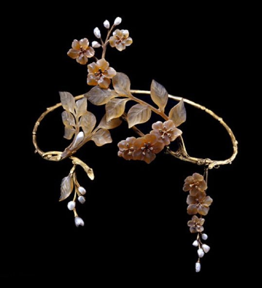 A French Art Nouveau horn, pearl, diamond and gold tiara. Comprising a wire work articulated band sculpted as a twig; and with two asymmetrical horn floral and foliate sprays converging in the front; the flowers with diamond-set stamens and with blister pearl sprays representing the buds. Maker's mark for Paul-Gabriel Liénard, and French control marks, circa 1905.