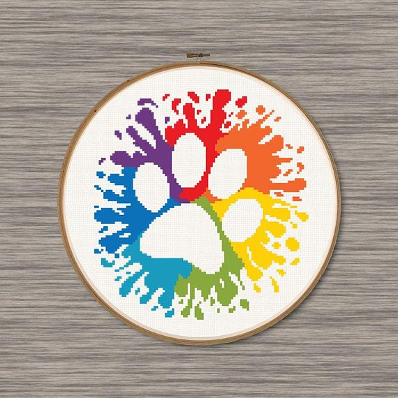 Instant download PDF cross stitch pattern of a dog paw with rainbow colored splatters.