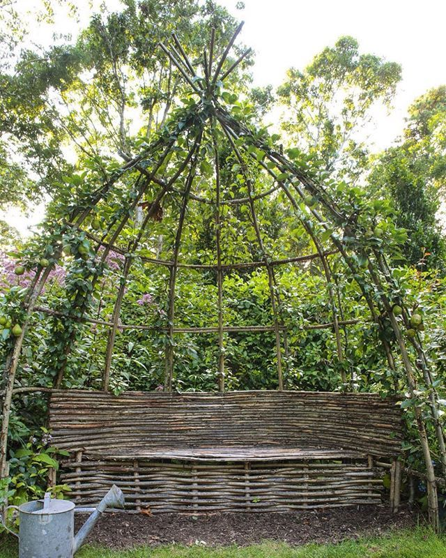 TAKE A SEAT. This completely fabulous hand woven willow arbour was designed by Gilles Guillot, head gardener at the famous Prieuré d'Orsan in Maisonnais in France, for garden officiando and renowned decorator @charmossny. It is particularly glorious as she is espaliering pears up the arched teepee like structure. To have this as a focal point in your country kitchen garden would be perfection. Source from @countrylifemagazine. #arbour #willowarchitecture #willowseat #gardenseat…