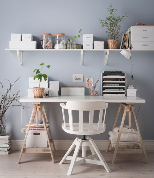 An organized desk without drawers in white and light wood with a shelf above it and lots of boxes, jars and vases for storage