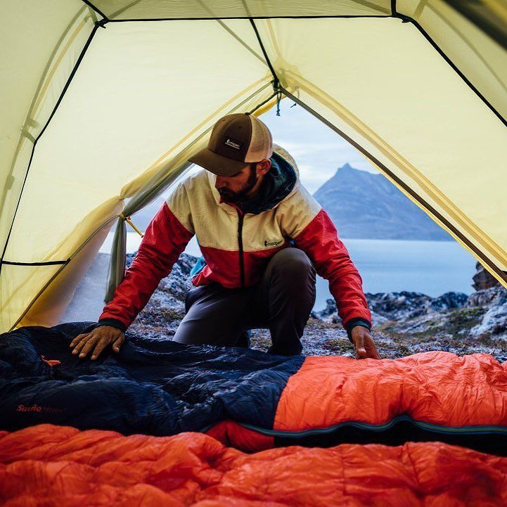 @yasso1am sets up camp after a day of paddling remote fjords near Tasiilaq, Greenland. : @chrisbrinleejr with @yasso1am in the Pacaya Insulated Jacket, laying out the Sueño Sleeping Bag. #GearForGood #Cotopaxi #AdventureOn