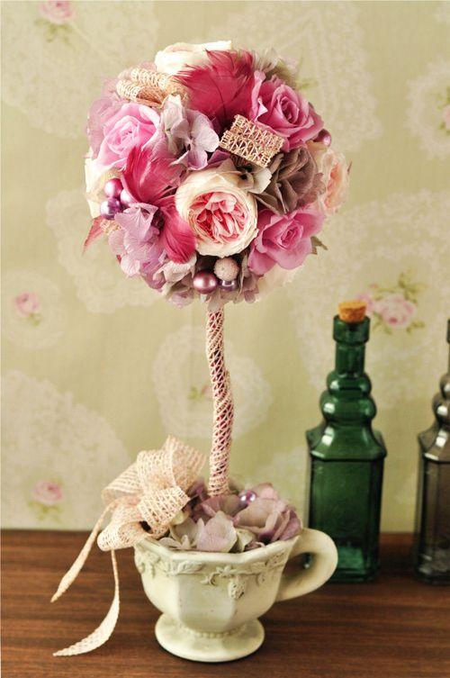 ピンクローズのフェミニントピアリーアレンジ。 ピンクの羽(フェザー)とラメパールがかわいらしさをいっそう引き立てます。  花器は素焼き陶器のアンティーク風カップでかわいらしく☆