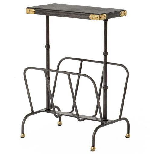Hardworking and versatile, this industrial iron side table boasts a magazine rack as a base. Finished with a faux leather black top, the piece has a 1940's library design. The tabletop corners and round feet are finished in polished brass, contrasting the eclectic ebony end table.