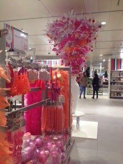 Het plaffond is versierd met een kerstboom die op zijn kop hangt. De roze en oranje versieringen springen eruit en zijn twee meter verderop gewoon in de schappen te vinden.