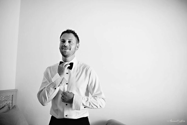 Groom putting on bow tie - Norway documentary wedding photographer