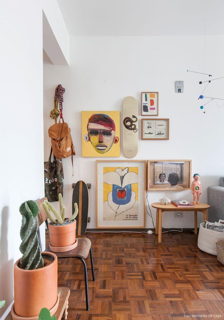 Piso de tacos, vasos de barro com cactos e parede galeria na sala de estar desse apê em SP.