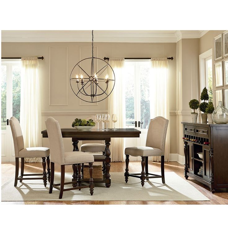Constructed of solid Asian hardwood, the Zachary Chic dining room set includes one oak brown solid hardwood dining table with turning legs and four counter height dining side chairs upholstered in beige linen fabric.