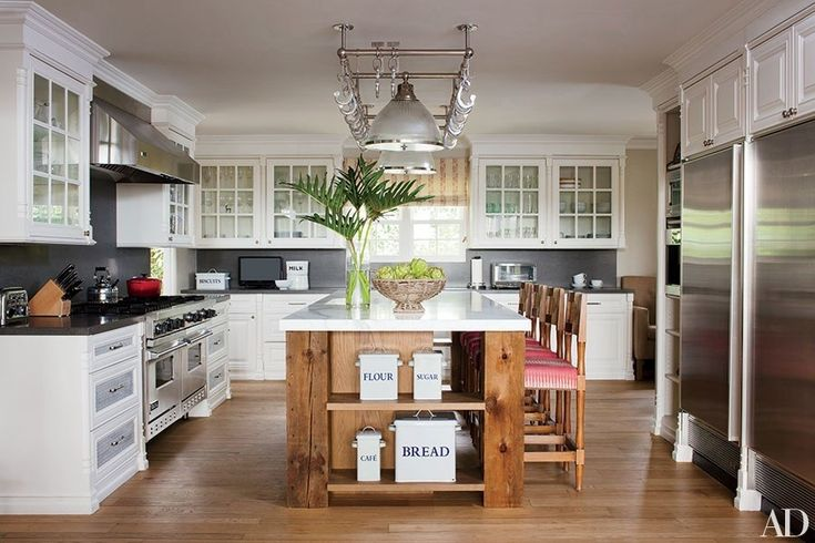Organization doesn't have to be boring: Use pretty storage containers on open shelves, like in this California kitchen, and consider a pot rack for easy access and visual interest.