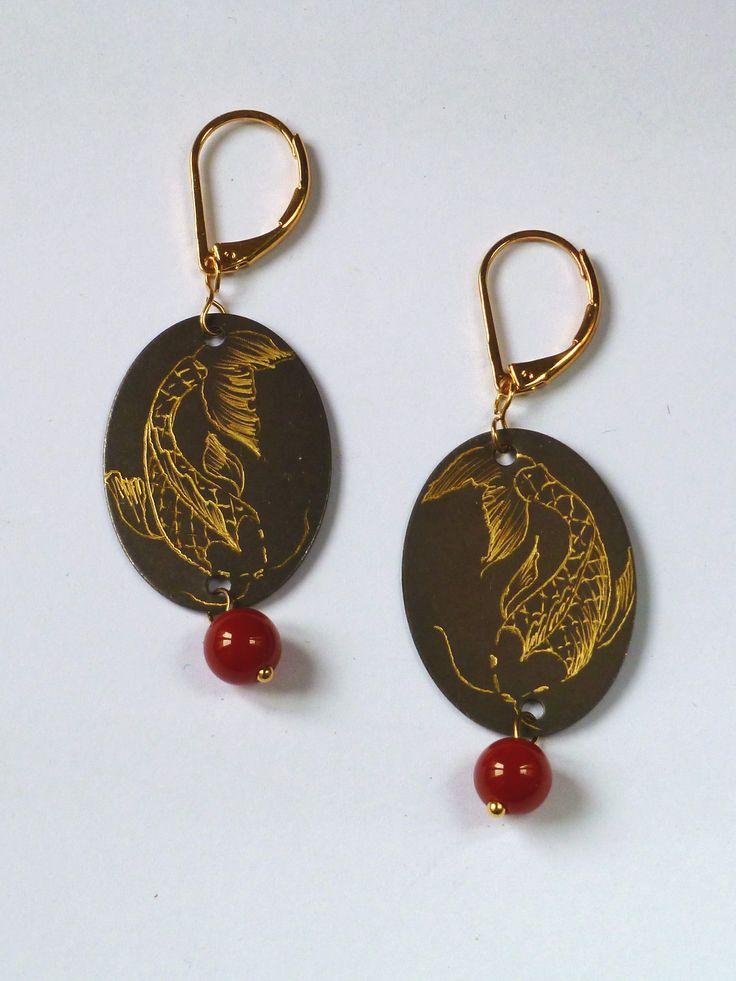 Boucle d'oreilles ovales serties de perles rouges.