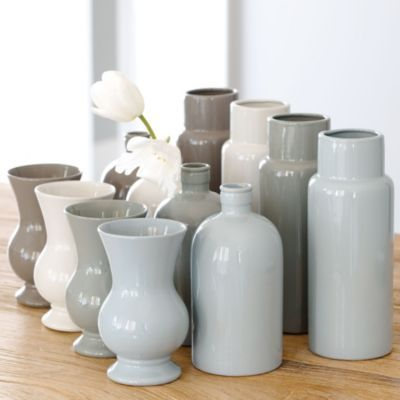 Monochromic vases are hot right now. And, they are great to use for dinner parties, a trio of three at a table w/ simple seasonal (again think monochromatic) flowers & greens with a few votives scattered round & you've got a contemporary table w/ a cool, urban vibe. Use simple white dishes and linens with linens that match the vases. Viola!