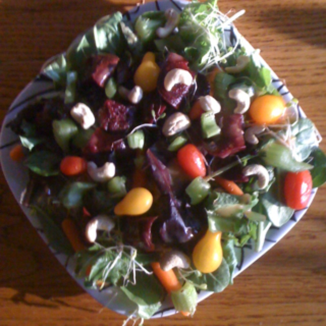 A summery sun dried tomato beet spinach and mixed green salad top off with cashews