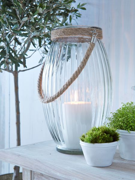 This elegantly rilled glass hurricane has a hint of marine style thanks to the natural rope detailing on its handle and around its rim.