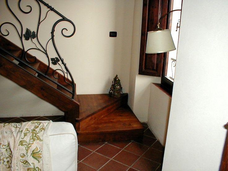 Scala portante in legno con parapetto e corrimano in ferro battuto