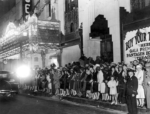 """Here's a bit of Hollywood history in the making. What we're seeing here is the opening of the Pantages Theatre on Hollywood Boulevard on June 4, 1930. The crowds gathered six bodies deep are there to see """"The Floradora Girl,"""" the movie was chosen to open the magnificent theater. Though hardly remembered anymore, it features a 7-minute finale filmed in 2-strip Technicolor, giving us rare color footage of its star, Marion Davies."""