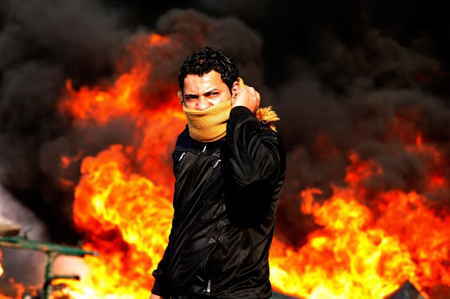 A protester stands in front of a burning barricade during a demonstration in Cairo, Egypt, on January 28, 2011. Police and demonstrators fought running battles on the streets of Cairo during four days of unprecedented protests by tens of thousands of Egyptians demanding an end to President Hosni Mubarak's three-decade rule. (Reuters/Goran Tomasevic)