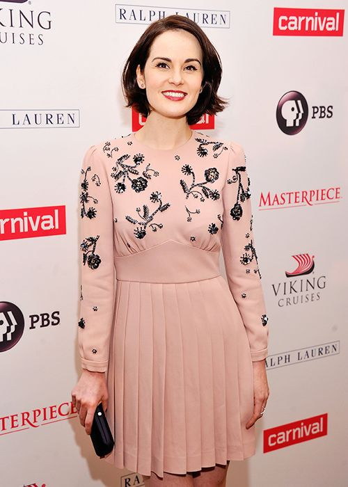 Salmon-colored knee length dress with black vines on the bodice. Actress Michelle Dockery.
