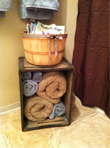 Old wooden crate for storing towels in guest bathroom.
