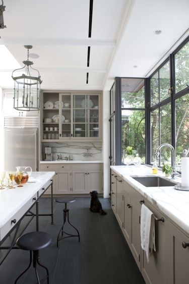 glass-front cupboard styling. Adore the black sash on the window wall. And the industrial stools. Awesome.
