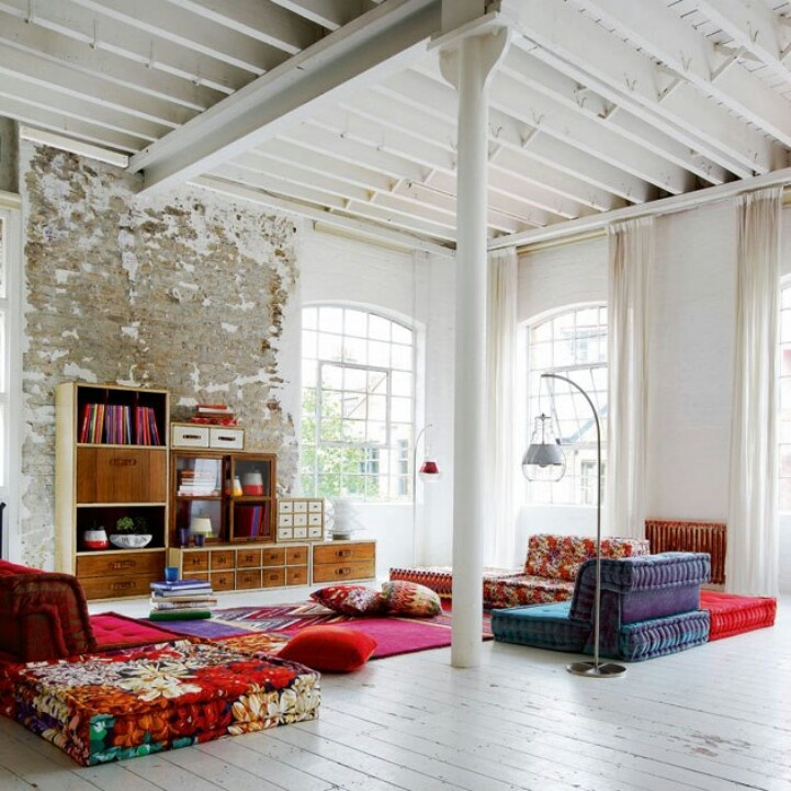 Warehouse living, open space, raggedy walls. Keep the area in White, as well as the long sheers on the windows; it gives a better visual  length to the room. Colors, lots of solids colors on sofas, cushions and pillows. Light wood for furniture to bring a natural feeling.