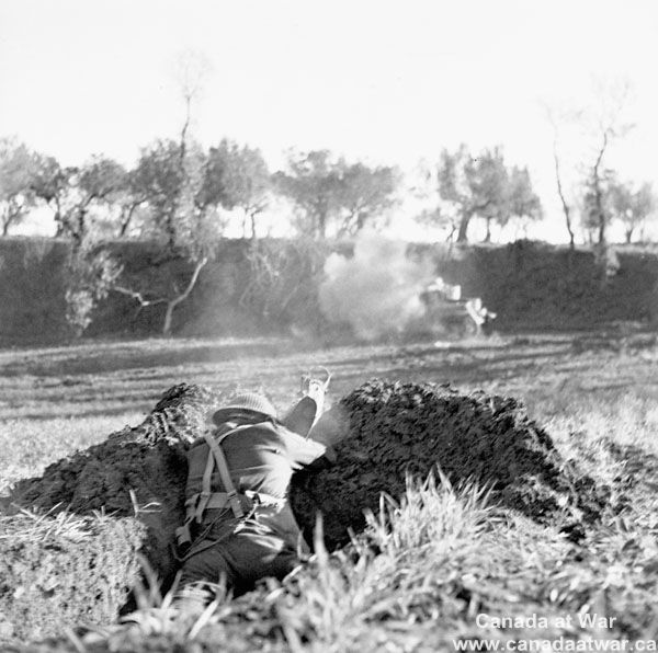 Ortona - An unidentified member of the West Nova Scotia Regiment firing a PIAT anti-tank weapon.