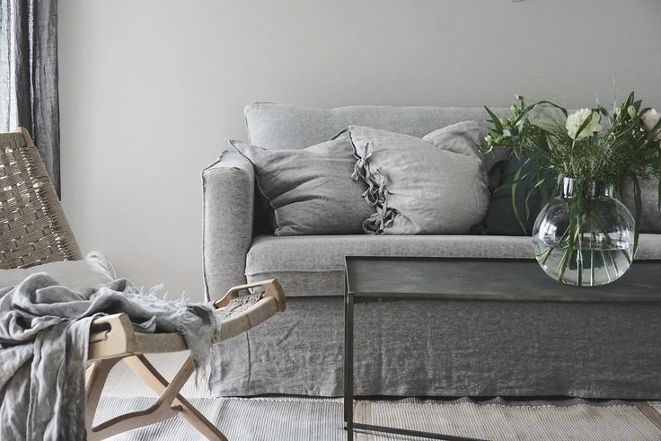 Grey Scandinavian inspired living room | grey linen sofa | simple yet perfectly styled bookshelf | Swedish photographer and stylist @baravickan updated her IKEA Karlstad sofa with a Bemz Loose Fit Urban cover in Graphite Brera Lino linen | rattan chair