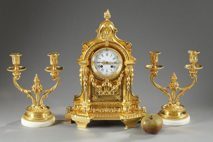 A 19th century gilt and chiseled bronze set composed of a mantel clock and a pair of candlesticks. The enamel dial, signed Raingo Frères in Paris, indicate the hours in... 3,400€
