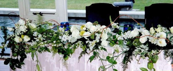 Table decoration with white and green flowers at a wedding by Kent Florist Mikiko Inoue