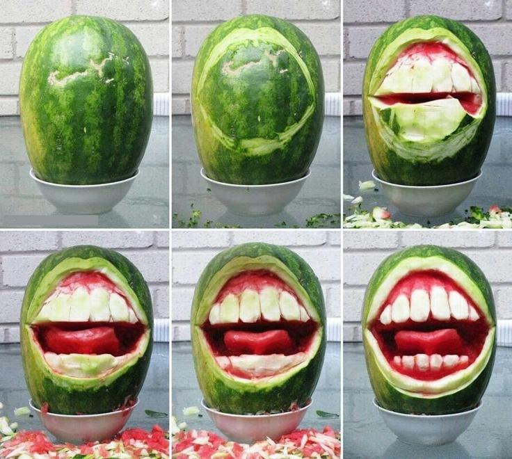 Ein Lächeln geschnitzt aus Wassermelonen. Strahelnd weiße Zähne stehen auch der Wassermelone.