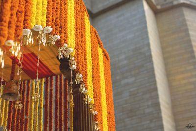genda phool decor, orange and yellow hanging flowers, hanging kaleere decor