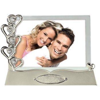 Hama. Portrétový rámeček Las Vegas 10 x 15 cm. - stolní portrétový rámeček - pro fotografie formátu 10x15 cm - reflexní sklo - materiál kov - barva stříbrná - možnost vyrytí data svatby - orientace fotografie na šířku. Foto Dolejš cena 483 Kč.