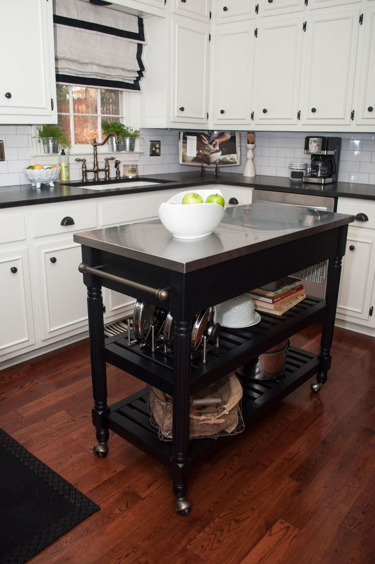 Smaller white kitchen with dark portable kitchen island on wheels. Good use of high cabinets.