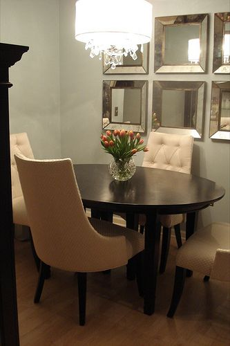 great small dining room - gray walls, mirrors on the wall, tufted seating