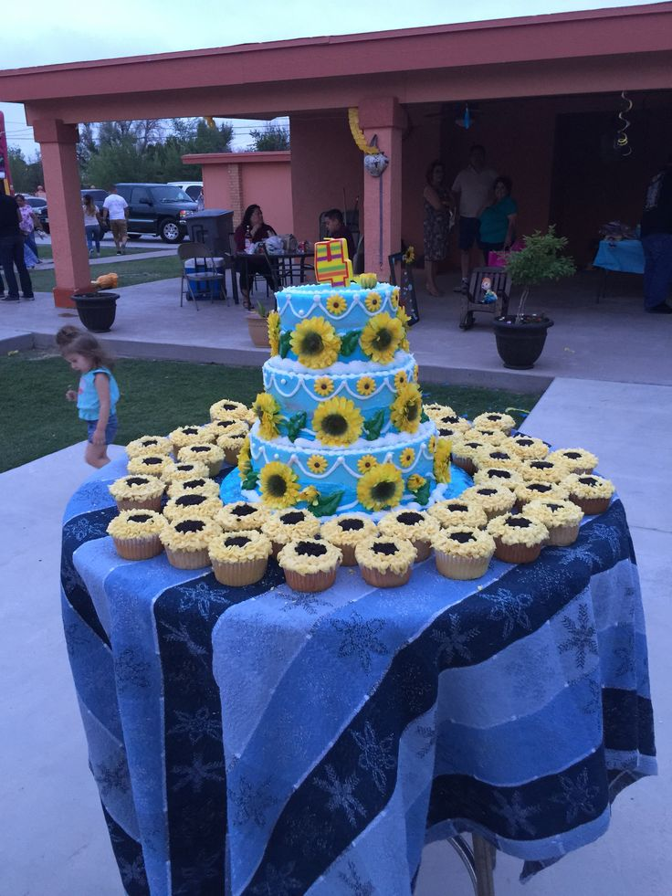Three tier Frozen Fever cake with sunflower cupcakes